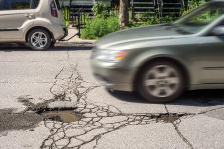 カナダ、モントリオール通りに近づいている車と大きな深い路面の穴。 写真素材