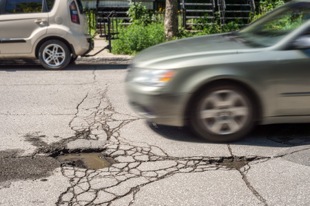 approaches: Large deep pothole with car approaching in Montreal street, Canada.