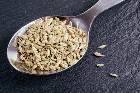 Fennel seeds in a fork on slate tile with faded effect Stok Fotoğraf