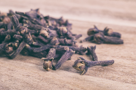 faded: Cloves on wood background with faded effect