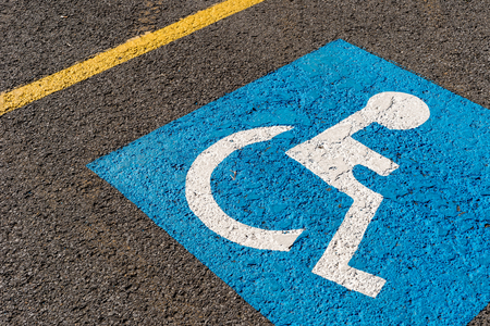 disabled blue parking sign painted on dark asphalt in Canada Stock Photo