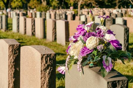 夕暮れ背景の墓石と墓地に花