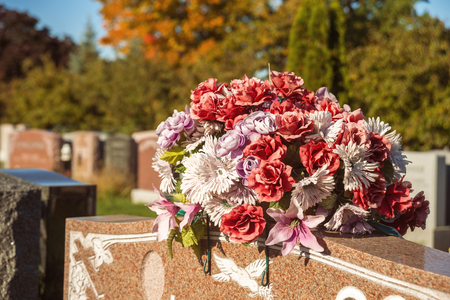 Flowers in a cemetery with headstones in the background at sunset Stock Photo