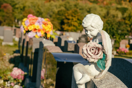 Statue of an angel holding a rose sitting on a tombstone in a cemetery with flowers and headstones in the background
