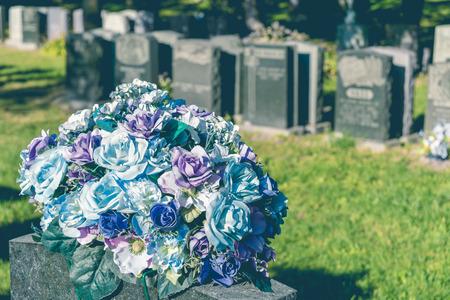 배경 (퇴색 한 복고풍 효과)에있는 기둥을 가진 묘지에있는 장미 스톡 콘텐츠