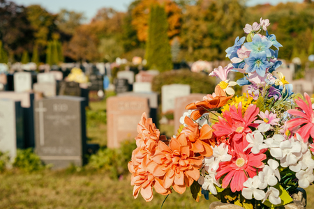 gravesite: Flowers in a cemetery with headstones in the background at sunset Stock Photo
