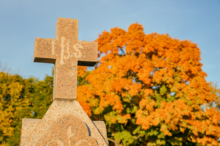 Cross in a cemetery with large maple tree in the background, in Autumn (Beloeil, Quebec, Canada) Stock Photo