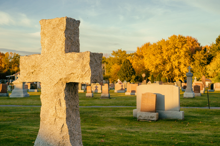 Cross in a cemetery with large maple trees in the background, in autumn (Beloeil, Quebec, Canada)