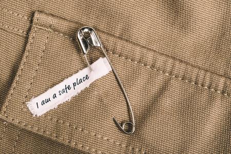 """El pasador de seguridad en la ropa con la etiqueta """"Estoy un lugar seguro"""" como un símbolo de la solidaridad"""