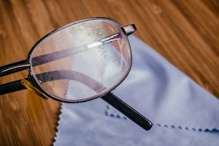 Old Eyeglass with many scratches and blue microfiber cloth Stock Photo