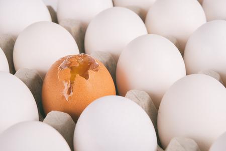 broken eggs: Broken brown egg among white eggs. Bullying concept.