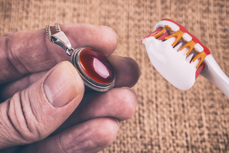 Cleaning silver jewellery with toothpaste and toothbrush Stock Photo