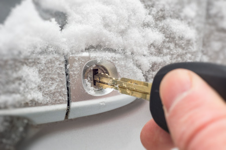 Close-up of a key inserted into the lock of frozen car door in winter Stockfoto