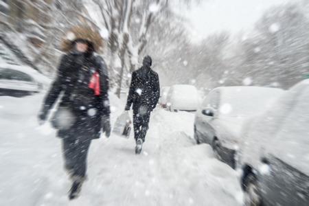 Snowstorm in Montreal. Pedestrians walking on sidewalk with motion blur effect