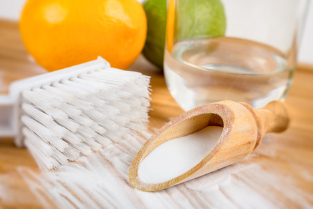 bicarbonate: Baking soda in a wooden spoon next to a brush, two lemons and a glass of water Stock Photo