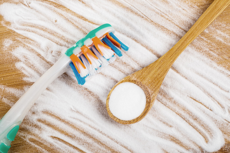 Baking soda in a wooden spoon next to a tooth brush