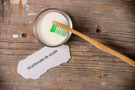 antacid: Baking soda next to a tooth brush on a wooden board. Bicarbonate de soude means baking soda in french.