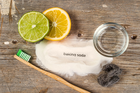 Baking soda, water, lemon, sponge, toothbrush and steel wool - Bicarbonate de soude means baking soda in french. Stock Photo