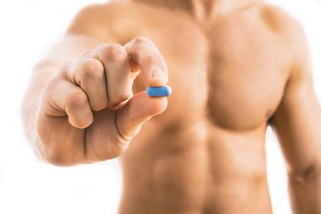 白い背景に分離された青い錠剤を保持している筋肉の若い男。