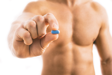 Muscular young man holding blue pill isolated on white background.