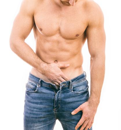 Spier jonge man die jeans draagt Geïsoleerd op een witte achtergrond. Stockfoto