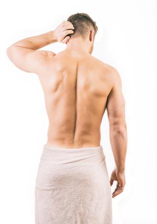 Achteraanzicht van een gespierde jonge man die een handdoek draagt