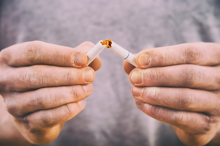 Quit smoking - male hand crushing cigarette Imagens
