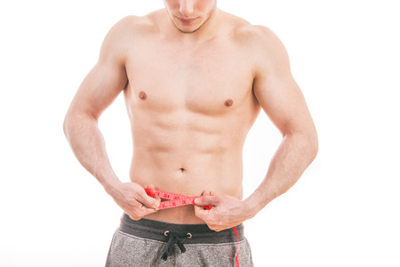 Male torso and red tape measure on white background Stock Photo