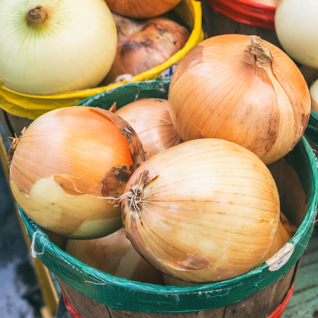 square root: Yellow onions in baskets at the market with vintage effect