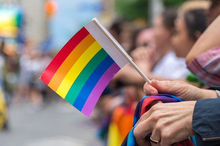 canadian flag: Gay Pride Parade spectator holding small gay rainbow flag during Toronto Pride Parade in 2017 Stock Photo