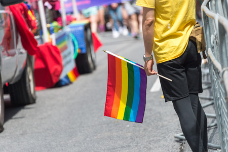 GayPride spectator holding rainbow gay flags during Toronto Pride Parade in 2017 Stock Photo