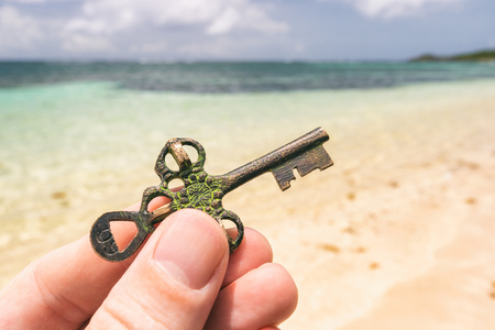 Hand holding a Treasure key found on a tropical beach. Opportunity or Mystery concept.