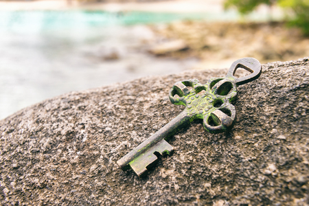 Treasure key lost on rock at the beach. Opportunity or Mystery concept. Stockfoto