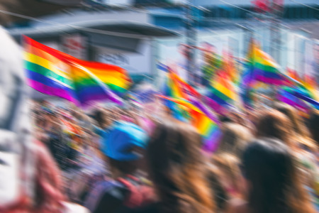 homophobia: Motion blurred picture of a gay rainbow flag during pride parade. Concept of LGBT rights.