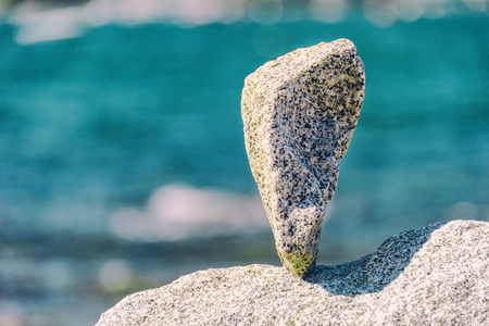 Triangular rock balanced on the tip in Vancouver rock stacking garden
