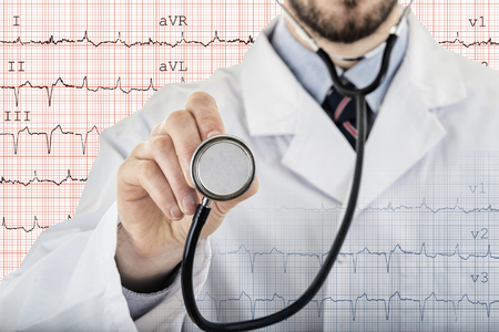 Male cardiologist doctor showing stethoscope for checkup with electrocardiogram in background Reklamní fotografie