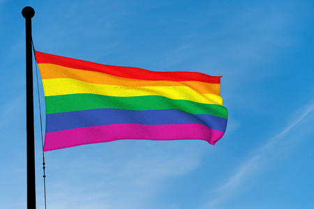 Gay Rainbow Flag waving over blue sky (3D rendering) Stock Photo