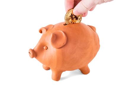 Hand inserting a Bitcoin coin into a piggy bank Reklamní fotografie