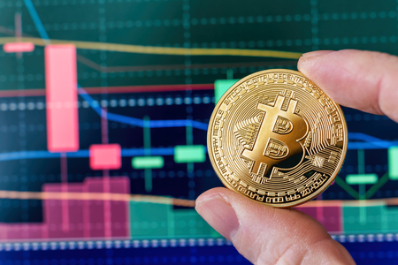 Hand holding a Bitcoin coin in front of a screen showing candlestick trading charts