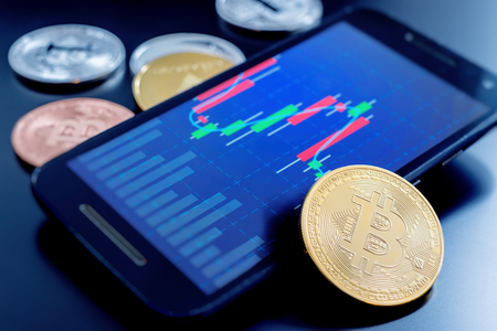 Cryptocurrency coins next to a cell phone showing candlestick chart Stock Photo