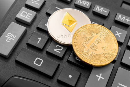 Montreal, CA - 17 May 2018:  Cryptocurrency coins (Bitcoin and Ethereum) over calculator. Reklamní fotografie
