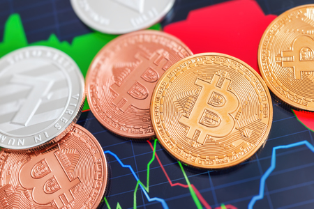 Cryptocurrency Bitcoin and Litecoin coins over tablet screen