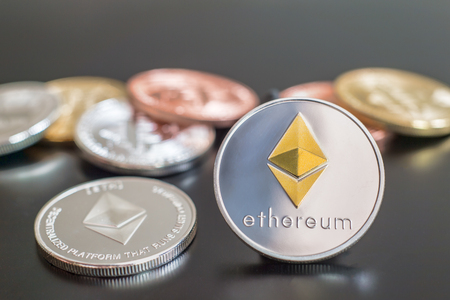 Cryptocurrency Ethereum metallic coins over grey background