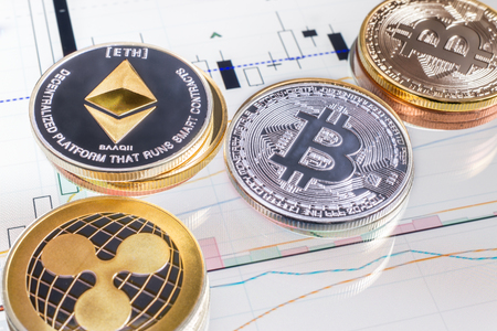 Montreal, CA - 16 April 2018:  Cryptocurrency coins over tablet screen showing candlestick chart. Bitcoin, Ethereum and Ripple are the top 3 Cryptocurrencies by Market Capitalization. Reklamní fotografie