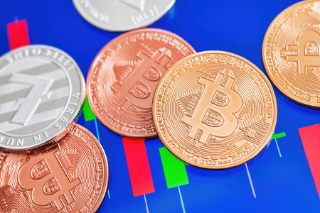 Cryptocurrency Bitcoin and Litecoin coins over tablet screen showing candlestick chart.