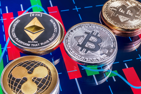 Cryptocurrency coins over tablet screen showing candlestick chart. Bitcoin, Ethereum and Ripple are the top 3 Cryptocurrencies by Market Capitalization.