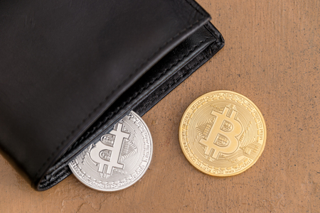 Two cryptocurrency Bitcoin metallic coins coming out a leather wallet