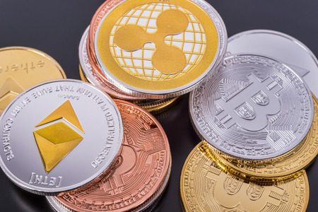 Montreal, CA - 16 April 2018: Stacked Bitcoin, Ethereum and Ripple coins over tablet screen.  Bitcoin, Ethereum and Ripple are the top 3 Cryptocurrencies by Market Capitalization.