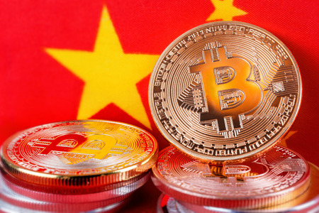 Bitcoin real coins over chinese flag fabric Reklamní fotografie