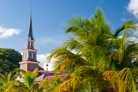 Petite Anse dArlet village in Martinique, with Saint Henri Church and palm trees Reklamní fotografie